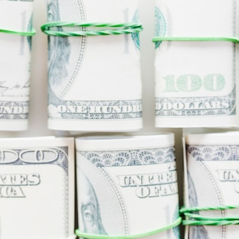 Arrotolato cento dollari americani legati con gomma verde