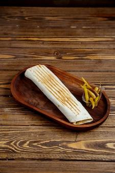 Arrotoli il pane e il peperoncino della pita su un vassoio di legno