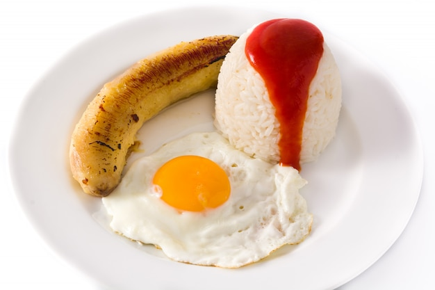Arroz a la cubana riso cubano tipico con banana fritta e uovo fritto su un piatto su bianco