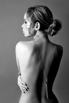 Art of nude fashion bionda schiena nuda su muro grigio, collana pendente su catena sul retro. bellezza e cura della pelle del corpo perfetto. la donna abbraccia le sue mani