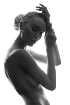 Arte aggraziata ragazza bionda in posa erotica, pelle pulita e liscia, sguardo pensieroso di donna.