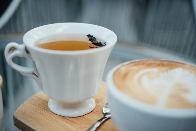 Arte calda del latte in tazza di caffè sulla tavola di legno in caffetteria