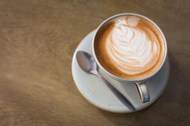 Arte calda latte caffè in una tazza e computer portatile sul tavolo di legno