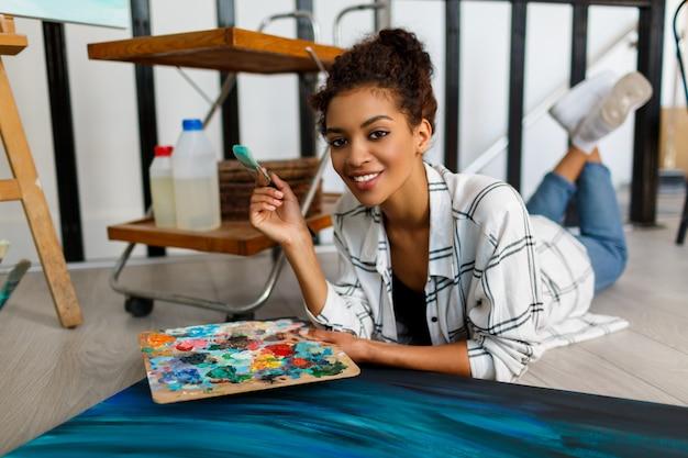 Arte contemporanea. talento e creatività. giovane signora nera ispirata che lavora al suo materiale illustrativo dell'estratto dell'oceano.