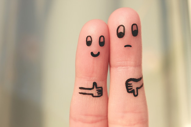 Arte del dito di coppia. donna che mostra i pollici in su e uomo che mostra i pollici in giù.