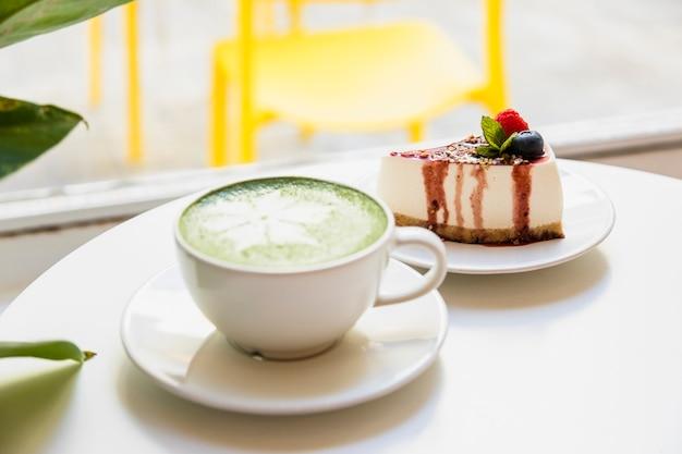 Arte del latte con il matcha e la cheesecake giapponesi del tè verde sulla tavola bianca