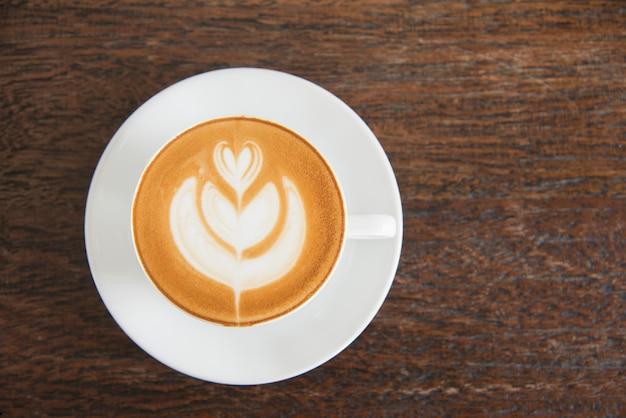 Arte del latte della tazza di caffè con la vista superiore della schiuma di forma del focolare sul fondo di legno della tavola in caffetteria