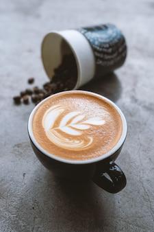 Arte del latte e chicco di caffè caldi sulla tavola nera