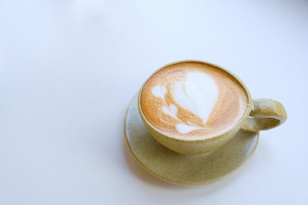 Arte del latte in tazza su sfondo bianco, copia spazio e vista dall'alto
