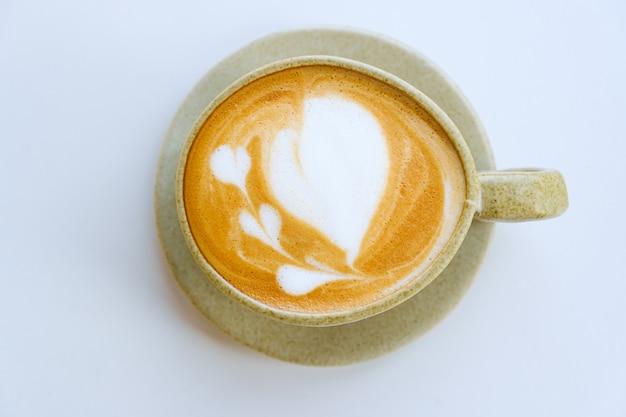 Arte del latte in tazza su sfondo bianco, vista dall'alto