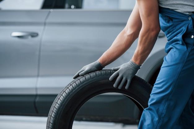 Arte del trasporto. meccanico che tiene un pneumatico al garage di riparazione. sostituzione di pneumatici invernali ed estivi