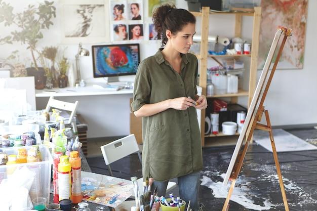 Arte e ispirazione. ripresa in interni di esitante giovane artista femminile che indossa jeans e camicia cachi in piedi nell'ampio interno dell'officina davanti al cavalletto, valutando la pittura che ha appena finito