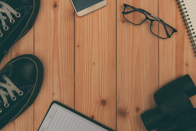Articoli da vacanza essenziali, scarpe da ginnastica, occhiali, smart phone, binocolo su legno