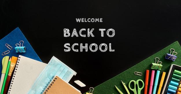 Articoli di cancelleria su sfondo nero. forniture scolastiche vista dall'alto per pubblicità e articoli promozionali. torna al concetto di scuola