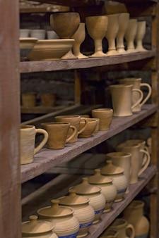Articoli in terracotta fatti a mano piatti sugli scaffali.