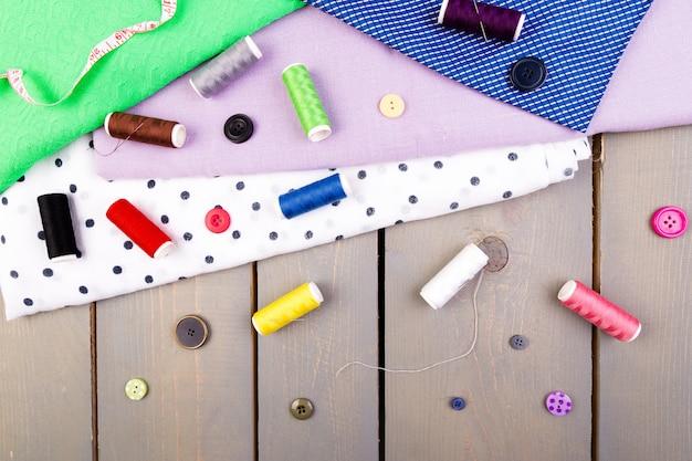 Articoli per cucire abiti. bottoni da cucire, rocchetti di filo e stoffa. vista dall'alto.