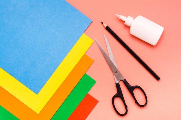 Articoli per fogli di creatività di cartone colorato, forbici, matita e colla sul rosso top view
