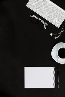 Articoli per ufficio bianchi e tazza di caffè sul desktop nero