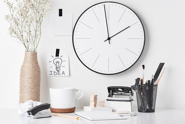 Articoli per ufficio ed orologio di parete su bianco