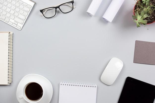 Articoli per ufficio sullo scrittorio grigio con spazio per la scrittura del testo