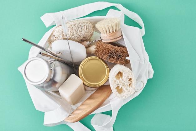 Articoli riutilizzabili in plastica privi di sacchetti in cotone. vaso di vetro, cannucce di metallo, bottiglia di alluminio e spazzola di pulizia di legno su verde