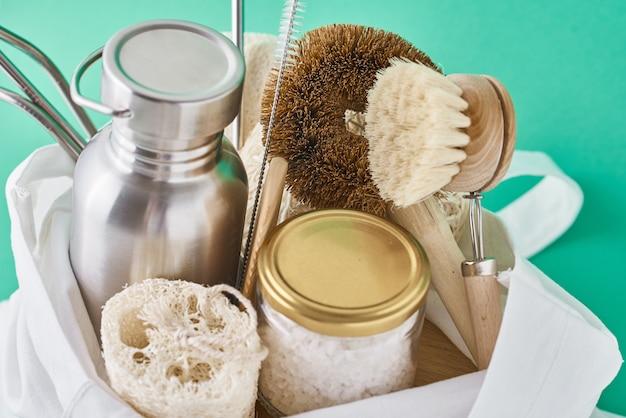 Articoli riutilizzabili in plastica privi di sacchetti in cotone. vaso di vetro, cannucce di metallo, bottiglia di alluminio e spazzola di pulizia in legno
