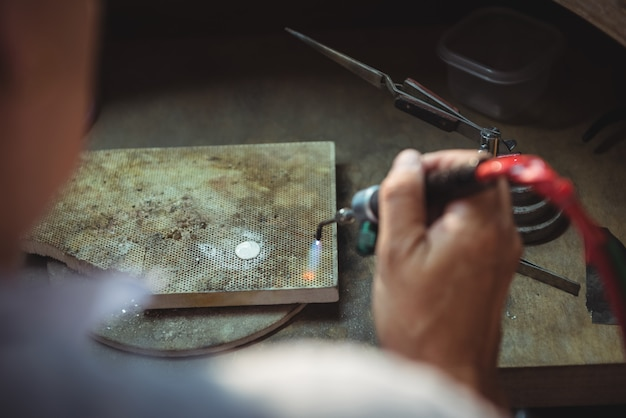 Artigiana che utilizza la torcia per saldature nell'officina