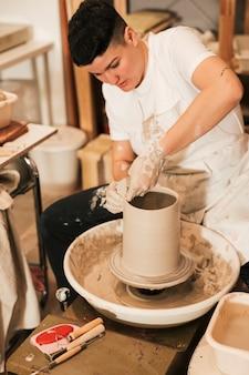 Artigiana della donna che forma un vaso di argilla su un tornio da vasaio