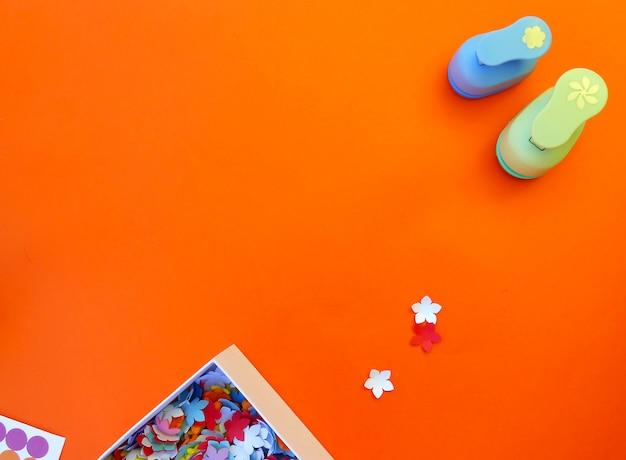 Artigianato con diversi perforatori e fiori di carta su uno sfondo arancione