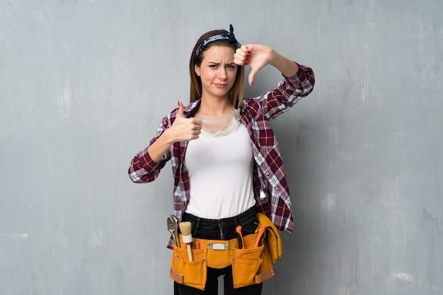 Artigiani o donna elettricista che fa un buon segno. indeciso tra sì o no