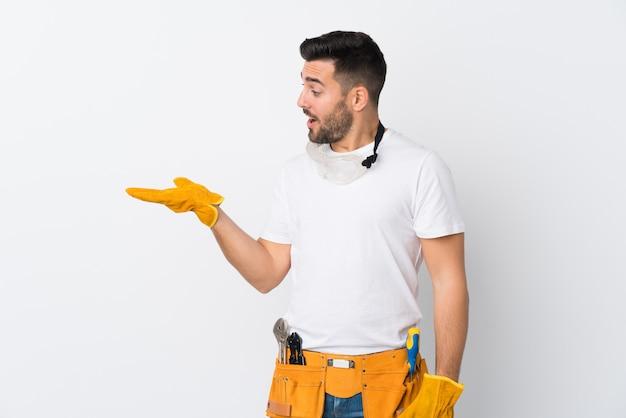 Artigiani o elettricista uomo isolato su bianco muro tenendo copyspace immaginario sul palmo