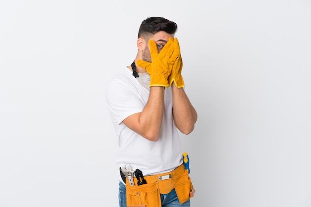 Artigiani o elettricista uomo sopra isolato muro bianco che copre gli occhi e guardando attraverso le dita