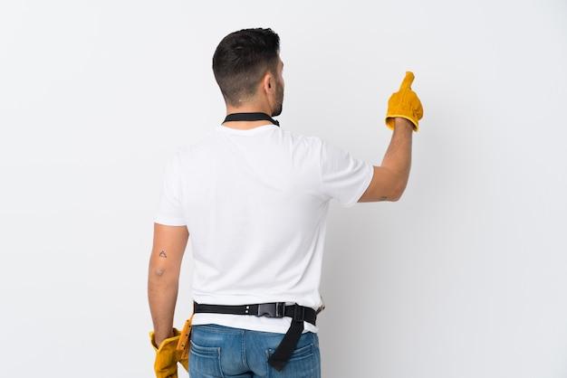 Artigiani o elettricista uomo sopra isolato muro bianco che punta indietro con il dito indice
