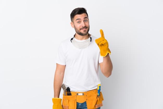 Artigiani o elettricista uomo sul muro bianco isolato che punta con il dito indice una grande idea