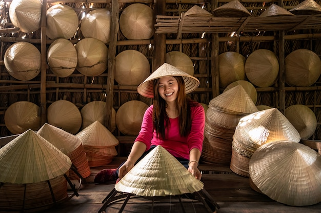 Artigiano femminile del viaggiatore asiatico che fa il cappello tradizionale del vietnam nel vecchio tradizionale