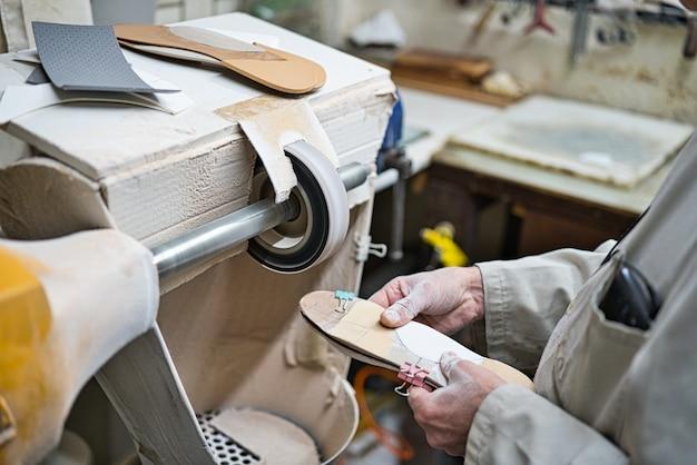 Artigiano professionista di solette ortopediche che lucidano, levigano e controllano nella sua officina la modellazione dei modelli con un tornio di carta vetrata. mani coperte di polvere.