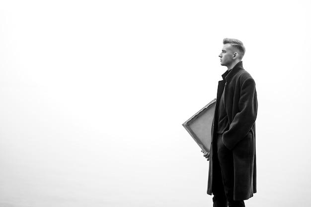 Artista all'aperto, giovane artista maschio cammina in autunno vicino al mare, foto in bianco e nero