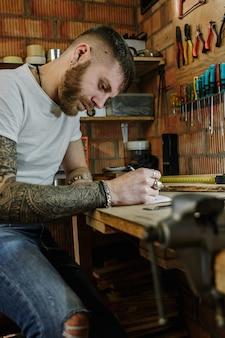 Artista artigiano che realizza un nuovo prodotto di design in legno nel suo laboratorio di casa.