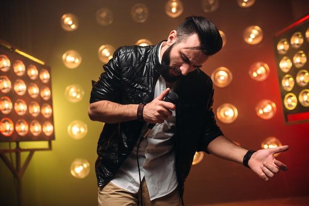 Artista barbuto con microfono canta una canzone