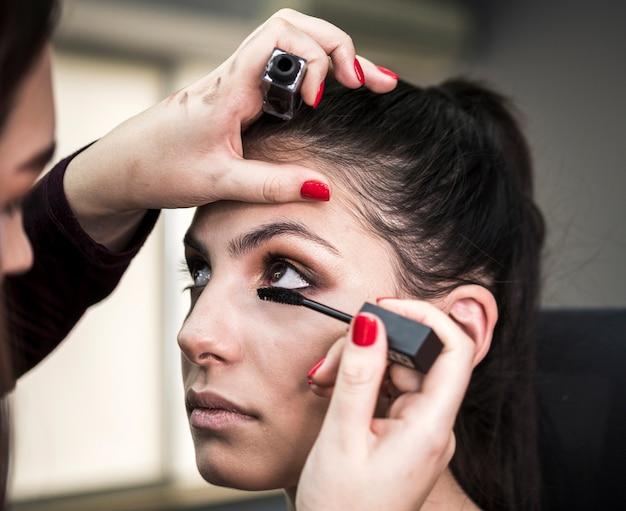 Artista che applica mascara sul modello carino