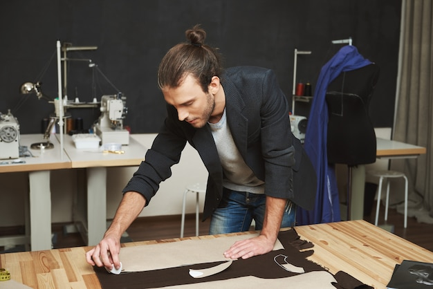 Artista che crea capolavoro. chiuda in su di giovane bello progettista di vestiti maschio con l'acconciatura alla moda e vestiti alla moda che lavorano al nuovo vestito con l'espressione concentrata del fronte.