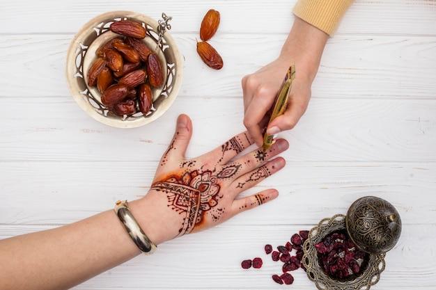 Artista che fa il mehndi sulla mano della donna vicino alla frutta delle date