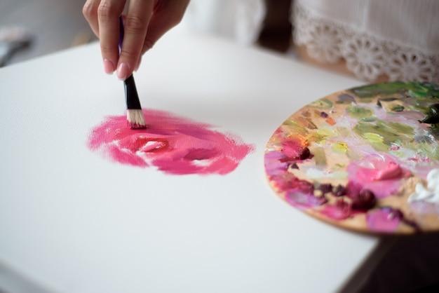 Artista della donna che disegna la sua immagine su tela con i colori a olio a casa