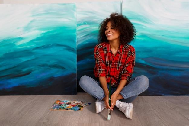 Artista della donna di colore in studio che tiene una spazzola. studente ispirato seduto sopra le sue opere d'arte.