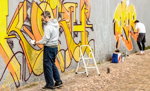 Artista di strada urbano che dipinge graffiti colorati