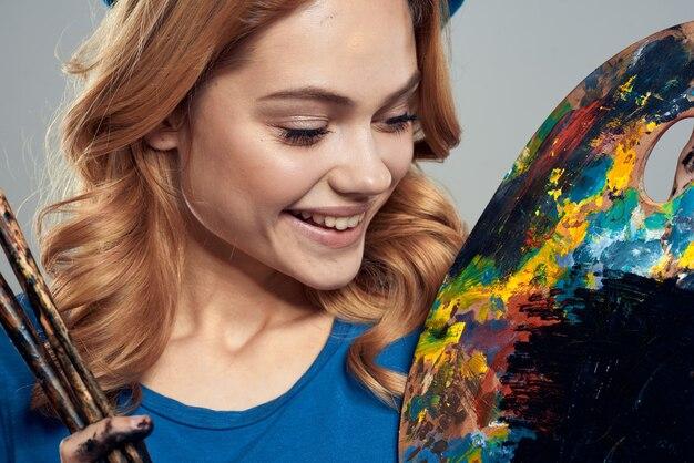 Artista donna dipinge un quadro su tela con un cavalletto