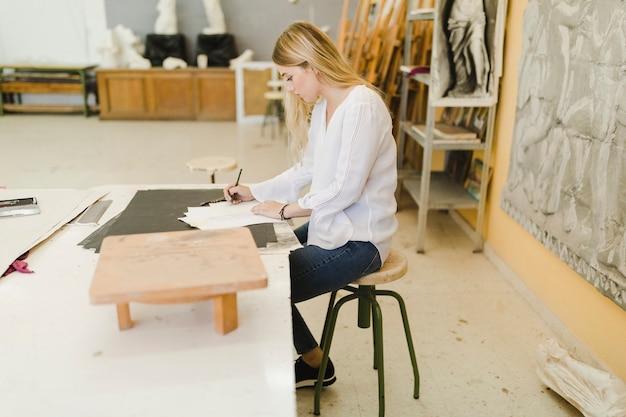 Artista femminile che schizza sulla carta all'officina