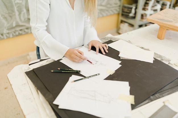 Artista femminile che schizza sulla carta con la matita sulla tavola