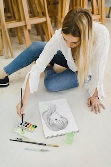 Artista femminile che si siede sulla pittura del pavimento sullo schizzo del fronte femminile