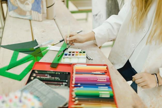 Artista femminile mescolando il colore dell'acqua dalla tavolozza con pennello